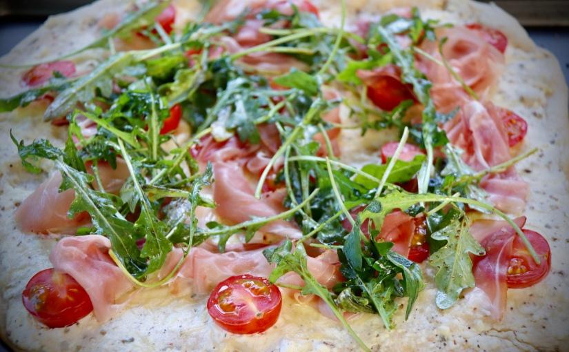 Pizza blanche au tomates cerises, roquette et jamboncru